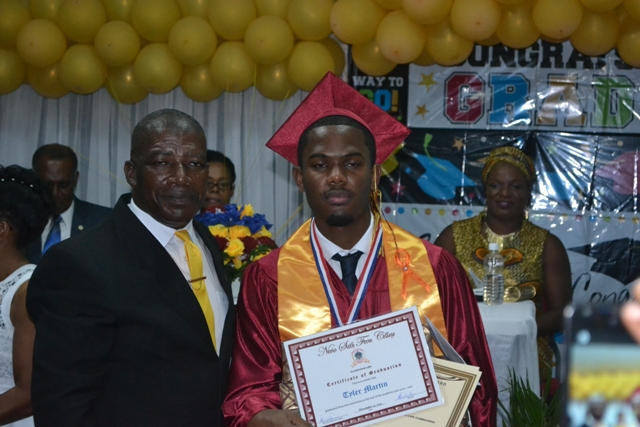 Valedictorian of the Nevis Sixth Form College Graduating Class of 2015 Tyler Martin with Principal Edson Elliot moments after he is presented with the Principal's Medallion at the Charlestown Secondary School and the Nevis Sixth Form College at their Graduation and Prize-giving Ceremony at the Cicely Grell-Hull Dora Stevens Netball Complex on November 11, 2015