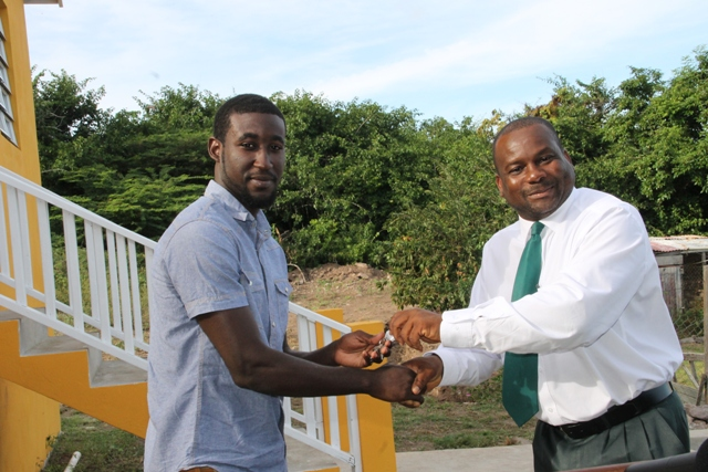 Adrian Williams receiving the keys to a two-bedroom furnished house, a gift from the Nevis Island Administration in collaboration with the Nevis Housing and Land Development Corporation, at the official Handing Over Ceremony at Eden Brown Estate on December 16, 2015