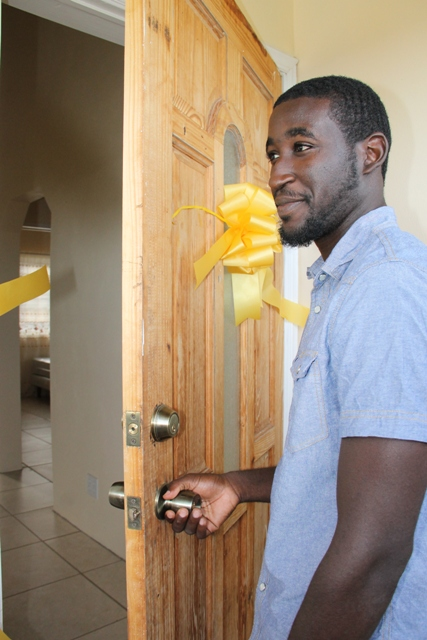 Nevis' most accomplished junior athlete Adrian Williams opens the door to his new home, a two bedroom furnished house at Eden Brown Estate after he was given the keys by Nevis Island Administration in collaboration with the Nevis Housing and Land Development Corporation at the official Handing Over Ceremony at Eden Brown Estate on December 16, 2015