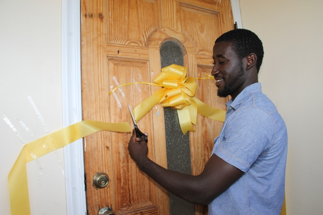 Adrian Williams cuts the ribbon to officially open his two-bedroom house moments after he was given the keys by Nevis Island Administration in collaboration with the Nevis Housing and Land Development Corporation at the official Handing Over Ceremony at Eden Brown Estate on December 16, 2015