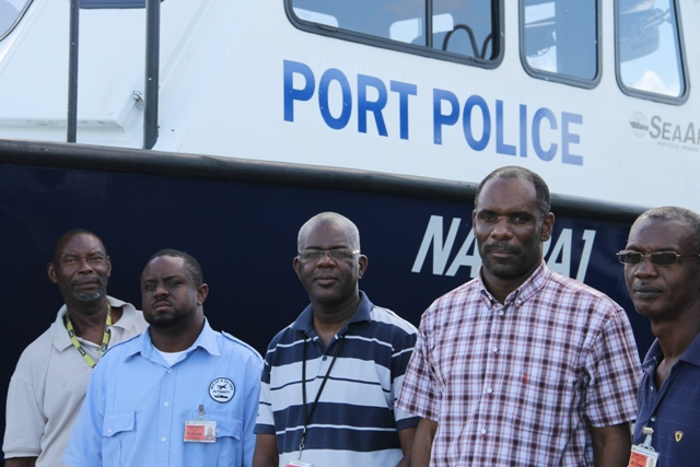 Chairman of the Nevis Air and Sea Ports Authority Board of Directors Colin Dore (second from right) flanked by (l-r) Audra Barrett and Dwaine Walters of the Marine Unit, Manager of the Nevis Air and Sea Ports Authority Oral Brandy and Head of the Unit Llewellyn Collins standing next to the replacement vessel at the Long Point Port on December 18, 2015
