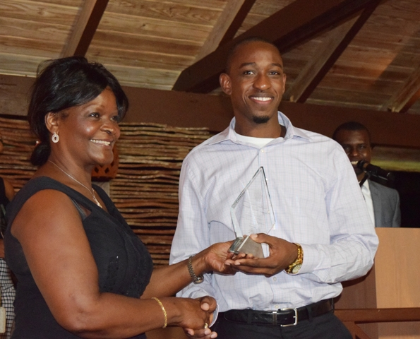 The Above and Beyond Award being presented to Jevon Claxton on behalf of Craig David by Premier of Nevis Hon. Vance Amory's wife Mrs. Verni Amory, at the first IT Delta Awards on December 19, 2015, at the Nisbet Plantation Inn