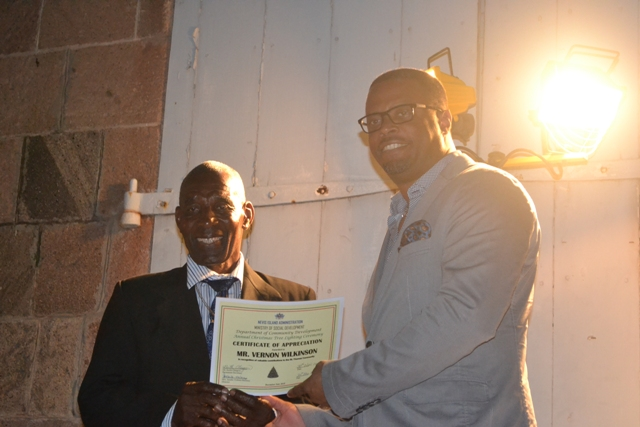 Minister of Social Development on Nevis Hon. Mark Brantley presents honouree Vernon Wilkinson of the St. Thomas Parish with a certificate of appreciation at the annual Charlestown Christmas Tree lighting Ceremony on December 02, 2015, for his outstanding contribution to the community