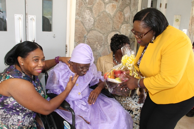 "Junior Minister in the Ministry of Social Development Hon. Hazel Brandy-Williams presenting a fruit basket to Celian ""Martin"" Powell on the occasion of her 104th birthday on behalf of the Ministry of Social Development at the Flamboyant Nursing Home on January 19, 2016. Powell is flanked by (left) her first granddaughter Kathleen Rawlins and (right) her daughter Dulcina Browne"