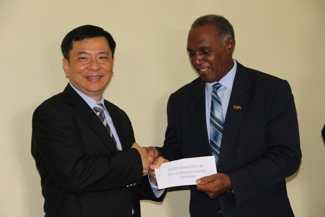 Republic of China (Taiwan) Ambassador to St. Kitts and Nevis His Excellency George Gow Wei Chiou (l) handing over a US$50,000 cheque, for the Nevis Cultural Development Foundation, to Premier of Nevis Hon. Vance Amory on April 19, 2016, at his Bath Hotel office