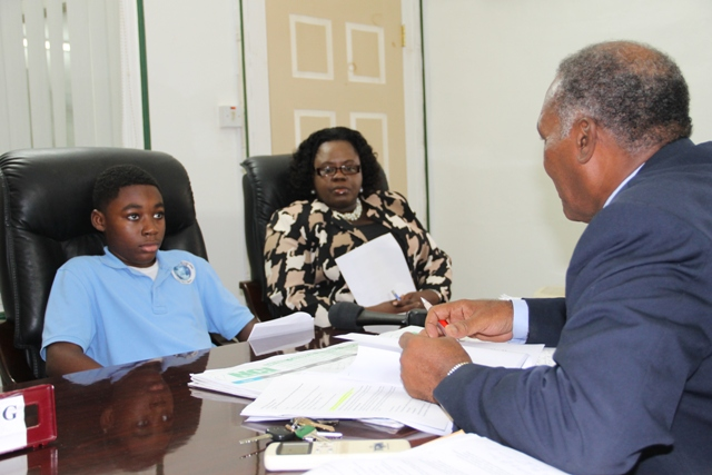 Premier of Nevis Hon. Vance Amory interacts with Jayden Dore, a student of the Nevis International Secondary School at his Bath Hotel office on April 19, 2016, after Jayden's presentation of a desalination proposal for Nevis, while Junior Minister of Youth and Sports Hon. Hazel Brandy-Williams looks on
