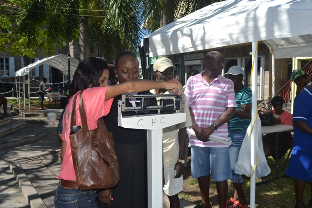 Head of the Nevis Health Promotion Unit Nadine Carty-Caines weighs a member of the public for the body mass index (BMI) information at the unit's free health screening activity on April 07, 2016, at the War Memorial in Charlestown in observance of World Health Day