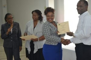 Permanent Secretary in the Ministry of Finance Colin Dore (right) presents a certificate of training to Vieda Mills at the closing ceremony of a Caribbean Development Bank funded training workshop at the St. Paul's Anglican Church Hall on April 14, 2016. Facilitators Catherine Forbes (left) and Nicole Liburd are assisting with presenting certificates to participants