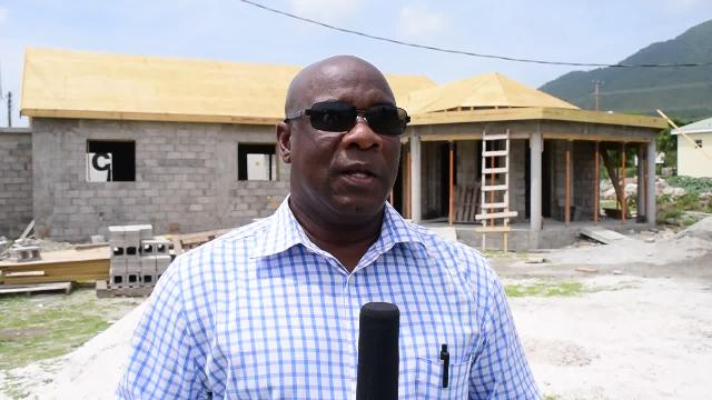 Minister of Agriculture on Nevis Hon. Alexis Jeffers at Prospect on April 27, 2016 with the new wing of the government-owned Abattoir under construction in the background