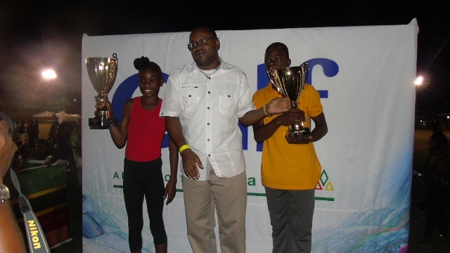 Director of Sports on Nevis Jamir Claxton presents trophies to (l) Tiana Liburd of the St. James Primary School and (r) Queleel Roberts of the Elizabeth Pemberton Primary School for Best Individual Performance at the 24th Gulf Insurance Athletics Championships at Elquemedo T. Willet Park on March 30, 2016