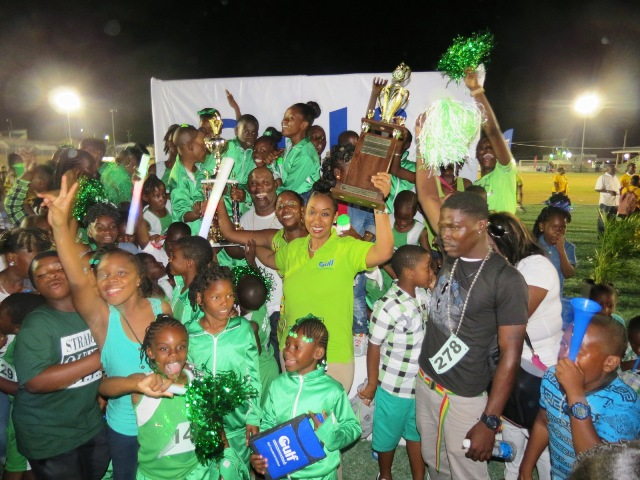 Students of the St. Thomas Primary School celebrate their win in Division A at the during the presentation ceremony at the end of the 24th Gulf Insurance Athletics Championships at Elquemedo T. Willet Park on March 30, 2016 with Marketing Manager of Gulf Insurance Ms. Lisa Hutson