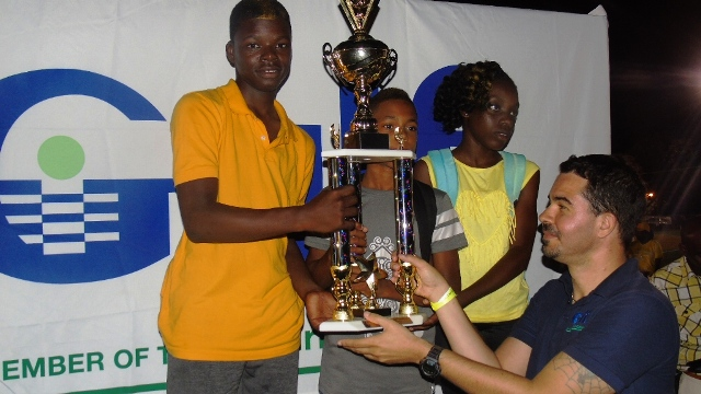 Students from the Elizabeth Pemberton Primary School accepting their winning trophy for Division B from a Gulf Insurance Representative during the presentation ceremony at the end of the 24th Gulf Insurance Athletics Championships at Elquemedo T. Willet Park on March 30, 2016 with Marketing Manager of Gulf Insurance Ms. Lisa Hutson