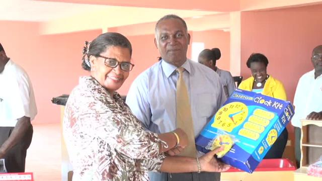 Premier of Nevis and Minister of Education Hon. Vance Amory receives gift of teaching materials from Ms. Sylvia Fahie, representative of donors Brenda and John Scanelli of Virginia at a handing over ceremony at the Department of Education on May 06, 2016