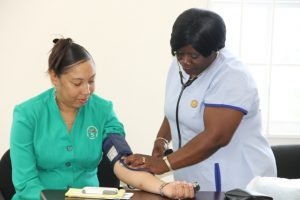Nurse Jean Tyson administers a blood pressure check to a staff member of the St. Christopher and Nevis Social Security Board branch in Nevis at Pinneys on May 17, 2016
