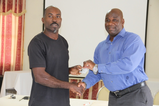 Minister of Agriculture Hon. Alexis Jeffers (r) presents a Farmers Identification Card issued by the Department of Agriculture to Ellis Philip, a farmer at a ceremony to launch the Farmer's Identification Card from the Department of Agriculture at the Red Cross conference room on May 24, 2016