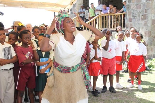 Adela Meade delivers a dramatic presentation depicting a day in the life of a slave at the New River Estate for students and seniors at New River Estate on May 18, 2016, at an event hosted by the Nevis Historical and Conservation Society and the Ministries of Tourism and Agriculture in observance of International Museum Day