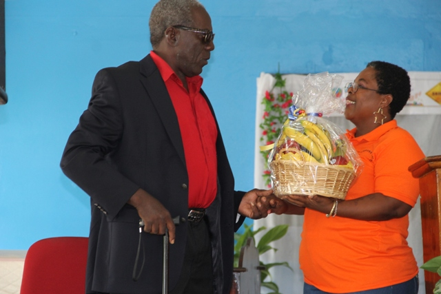 Ezzard Charles, Patron of Charlestown Secondary School Multi-Purpose Centre's Technology and Art Exhibition receives a fruit basket and plaque from teacher Ms. Mavis Parris on behalf of the Centre, at the opening ceremony on May 26, 2016