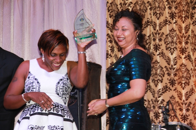 A visibly happy Melissa Seabrookes of the Four Seasons Resort receives the Hotel Manager of the Year Award from Mrs. Sharon Brantley, wife of the Minister of Tourism Hon. Mark Brantley, on behalf of the Ministry of Tourism at the Tourism Awards Gala and Dance at the Four Seasons Resort on May 28, 2016