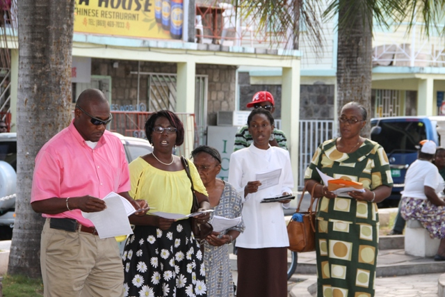 Brian Dyer, Director of the Nevis Disaster Management Department (extreme left) and Preacher Rev. Careen White-Richardson (second from right) join in song with other members of the community at the Nevis Christian Council's prayer service for God's protection during the 2016 hurricane season at the War Memorial Square in Charlestown on June 17, 2016