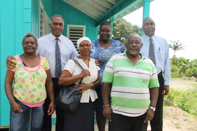 (L-r back row) Premier of Nevis Hon. Vance Amory flanked Pearl Smithen mother of Vanessa (extreme left), Cabinet Secretary in the Nevis Island Administration Stedmond Tross, (front row), Ms. Glorita Vaughn, Community Caregiver in the Ministry of Social Development, Senior Citizens Division responsible for Gingerland and contractor Phillip Walters standing on the doorsteps of a new home given to Vanessa Smithen (back row second from right) on June 24, 2016 by the administration