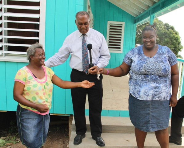 Premier of Nevis Hon. Vance Amory with Stoney Hill residents Vanessa Smithen (right) and her mother Pearl Smithen (left) moments after handing them the keys to a brand new home at Gingerland on June 24, 2016