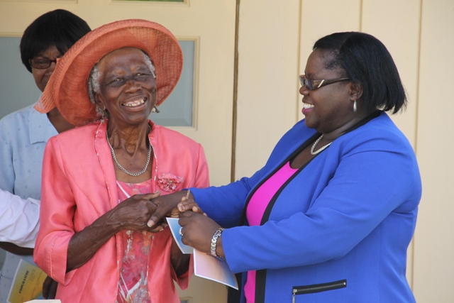 Marjorie Walters of Brick Kiln Village receives keys to her new home from Junior Minister in the Ministry of Social Development Mrs. Hazel Brandy-Williams on June 15, 2016, as part of the ministry's Community Housing Programme