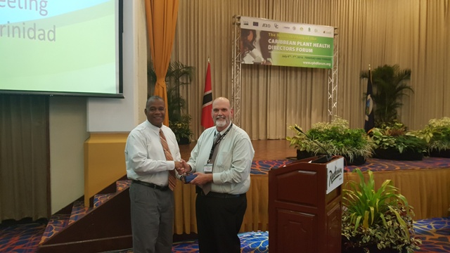 Dennis Martin (r), an official of the United States Department of Agriculture presents Eric Evelyn, with an award by the department at a recent meeting in Trinidad, for his contribution to the Caribbean Plant Health Directors Forum