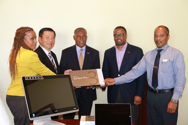Republic of China (Taiwan)'s Resident Ambassador to St. Kitts and Nevis His Excellency George Gow Wei Chiou (second from left) presents 25 computers, and three Microsoft Surface Pro 3 tablets to Premier of Nevis Hon. Vance Amory (third from right) and Deputy Premier of Nevis and Minister of Health Hon. Mark Brantley (second from right), Permanent Secretary in the Ministry of Health Nicole Slack-Liburd (extreme left) and Hospital Administrator Gary Pemberton (extreme right) at a handing over ceremony at the Alexandra Hospital conference room on July 25, 2016