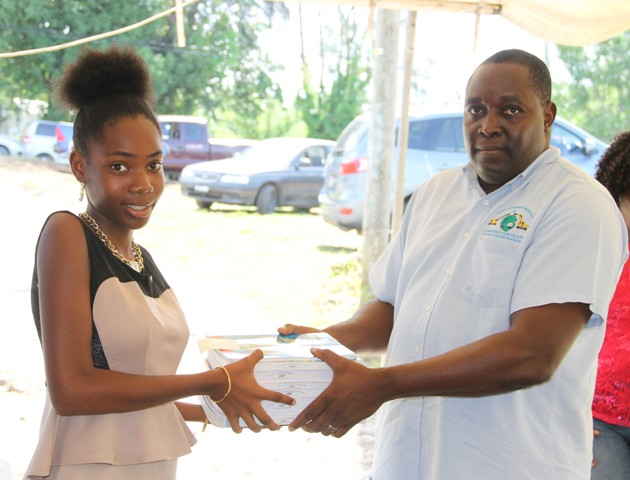 Robelto Liburd, Managing Director at LEFCO Equipment Rental and Construction Company Ltd. makes a special presentation to Adeilyah Moore of Ramsbury on August 15, 2016, as part of the Cane Garden Community Improvement Club Incorporated Text Book Initiative Drive