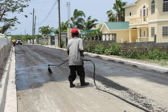 A members of the Public Works Department applies tar in preparation for asphalting on the Lower Farms Road on July 29, 2016