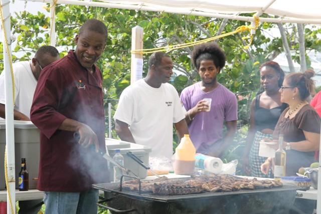 "Local chef Franklyn ""Cut"" Daniel from the Nevis Water Department Sports Club barbecuing with his special mango sauce at the Nevisian Chefs Mango Feast at Oualie Beach during the third annual Nevis Mango and Food Festival"