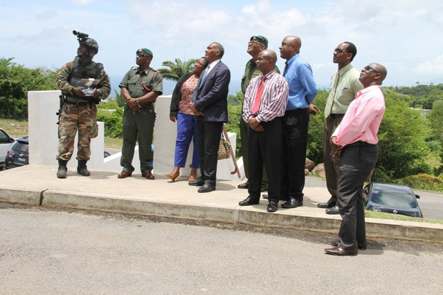 Nevis Island Administration officials witness a demonstration with drones by personnel from the Reserve Corps of the St. Kitts-Nevis Defence Force during a demonstration of crime fighting skills at a training camp at the Elizabeth Pemberton Primary School at Cole Hill on August 25, 2016. (Left-right back row) Drone technician, Captain Winslow Brookes, Principal of the Elizabeth Pemberton Primary School Shenelle Pemberton, Premier of Nevis Hon. Vance Amory, Commander of the St. Kitts-Nevis Defence Force Lieutenant Colonel Patrick Wallace, Cabinet Secretary Stedmond Tross, and Assistant Secretary in the Premier's Ministry Kevin Barrett. (Front row l-r) Permanent Secretary in the Premier's Ministry Wakely Daniel and Hon. Alexis Jeffers