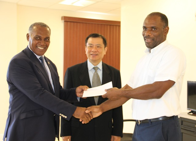 Premier of Nevis Hon. Vance Amory (left) hands over a cheque from the government and people of the Republic of China (Taiwan) at his Pinney's Estate office on September 30, 2016, to Colin Dore, Permanent Secretary in the Ministry of Finance in the Nevis island Administration (right) while Resident Ambassador of the Republic of China (Taiwan) to St. Kitts and Nevis His Excellency George Gow Wei Chiou looks on