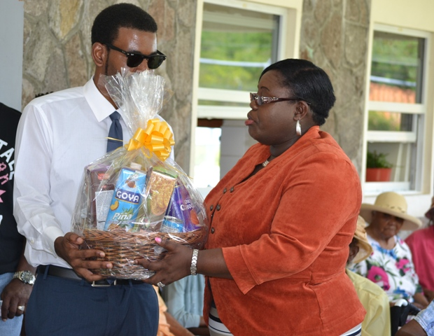 "Hon. Hazel Brandy-Williams, Junior Minister in the Ministry of Social Development on Nevis, presenting a gift basket to great grandson of 104-year-old Celian ""Martin"" Powell at a ceremony to recognise the oldest person in St. Kitts and Nevis on October 13, 2016 at the Flamboyant Nursing Home"