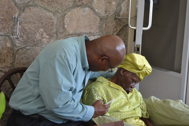 """Hon. Carlisle Powell shares a moment with his grandmother 104-year-old Celian """"Martin"""" Powell at a ceremony hosted by the Ministry of Social Development to recognise her as the oldest person in St. Kitts and Nevis at the Flamboyant Nursing Home on October 13, 2016, as part of activities for the Month of the Older Person"""