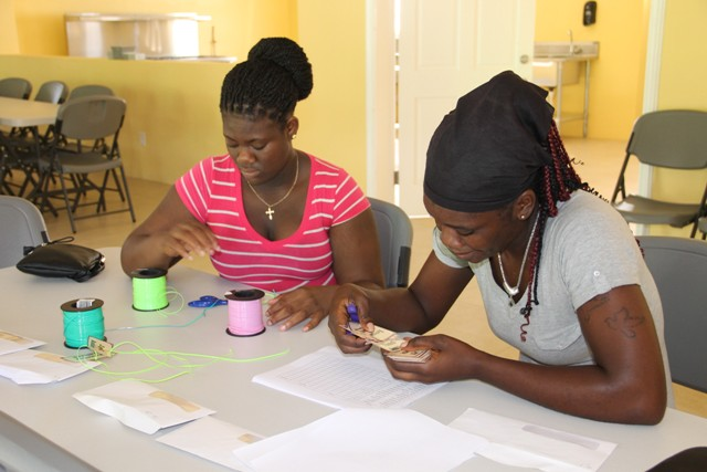 Other staff at the new Joycelyn Liburd Primary School (JLPS) cafeteria (l-r) Randelicia Chapman and Tesheba Freeman, preparing nametags for students on September 30, 2016, ahead of the first day of the School Meals Programme