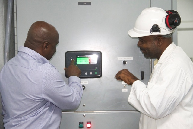 Hon. Alexis Jeffers, Minister of Communications, Works and Public Utilities (right) with Ivan Weekes, operator in the Generation Department at the controls commissioning the MP36 2.5megawatt generating set at Prospect Power Plant on December 21, 2016