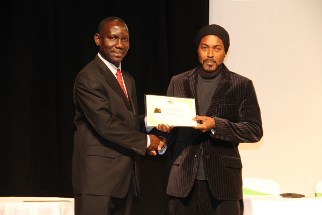 Photographer Sylvester Meade, the first winner of the Ministry of Tourism's Amateur Photographer of the Year contest accepting the winner's certificate from John Hanley, Assistant Secretary in the Ministry of Tourism at the awards ceremony in 2016 (file photo)