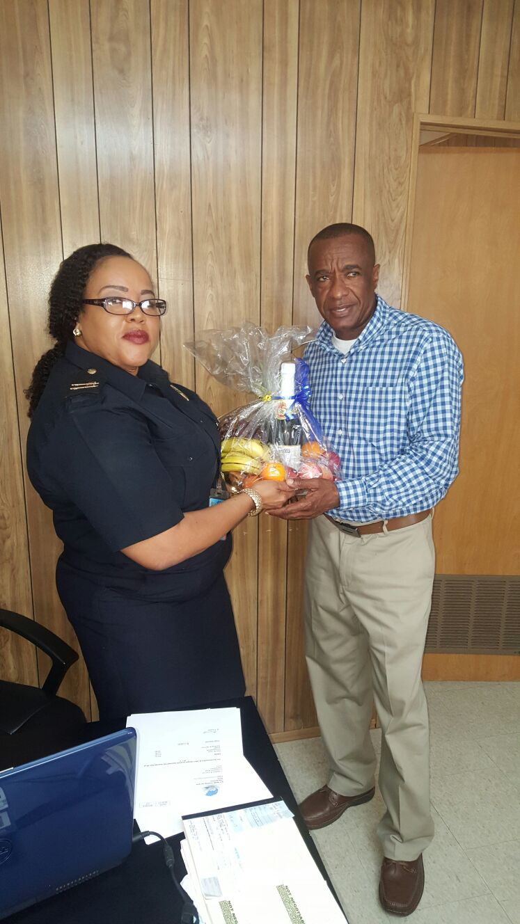 Wendy Wilkes, Senior Customs Officer at the Customs and Excise Department on Nevis presents a fruit basket to Vernon Evelyn, a past customs officer as a token of appreciation from the Department on International Customs Day on January 26, 2017