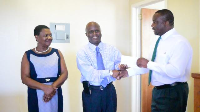 Keith Glasgow, Permanent Secretary in the Ministry of Social Development, representing the Nevisian Association of Washington DC presenting a cheque to Permanent Secretary in the Ministry of Education Wakely Daniel at the Department of Education recently, while Palsy Wilkin, Chief Education Officer in the Nevis Island Administration looks on