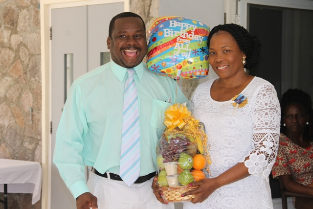 "Keith Glasgow, Permanent Secretary in the Ministry of Social Development presents a gift basket on behalf of the ministry and Department of Social Services to Mervette Powell, granddaughter of 105-year-old birthday girl Celian ""Martin"" Powell on behalf of her great-grandmother at a birthday celebration on January 19, 2017 at the Flamboyant Nursing Home"