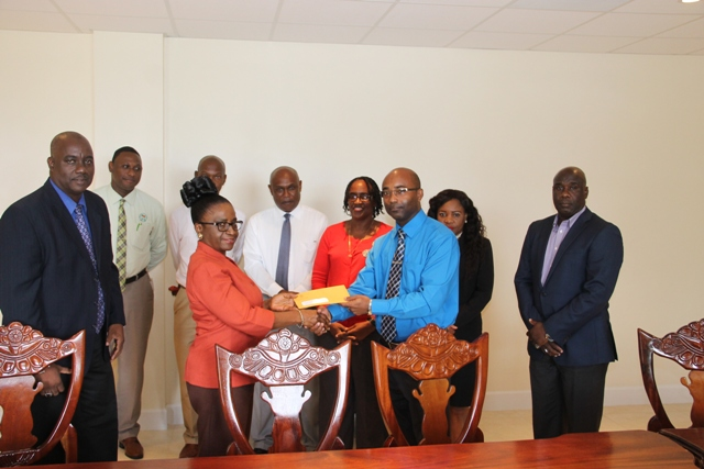 Director of Social Security Sephlin Lawrence, on behalf of the St. Christopher and Nevis Social Security Board, hands over $10M cheque to Dexter Boncamper, General Manager of the Nevis Housing and Land Development Corporation, at a brief ceremony at the Social Security conference room at Pinney's Estate on January 24, 2017. Looking on are (l-r) Chairman of the St. Christopher and Nevis Social Security Board of Directors Oscar Walters, Secretary to the Board Leon Charles, Deputy Director Steve Wrenford, Assistant Director of the Social Security Nevis Branch Vernel Powell, Board Member Jacqueline Brookes-Jeffers, Legal Counsel in the NIA Rhonda Nisbett-Browne and Hon. Alexis Jeffers, Minister responsible for Housing and Lands on Nevis and Chairman of the Nevis Housing and Land Development Corporation Board of Directors