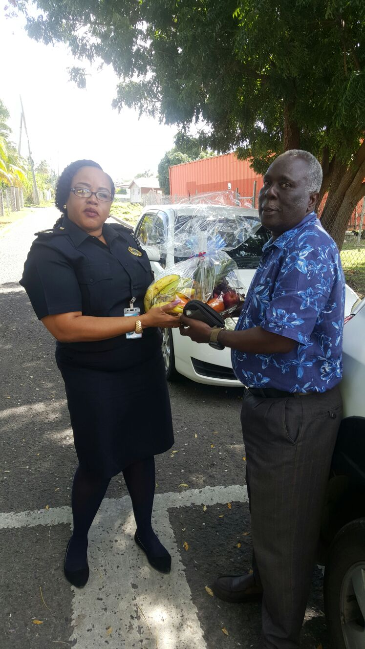Wendy Wilkes, Senior Customs Officer at the Customs and Excise Department on Nevis presents a fruit basket to Stephen Jones, a past customs officer as a token of appreciation from the department on International Customs Day on January 26, 2017