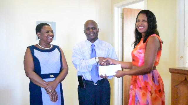 Permanent Secretary in the Ministry of Education Wakely Daniel accepting donations from Michele Pemberton, Treasurer of the Nevis Association of South Florida on behalf of her association and the Dr. Lornette Mills Charitable Fund at the Department of Education recently, while Palsy Wilkin, Principal Education Officer in the Nevis Island Administration looks on