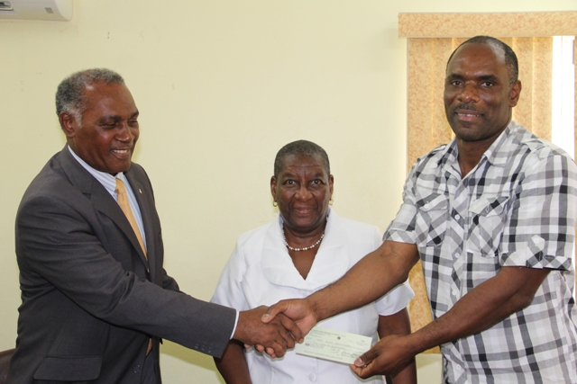 (l-r) Hon. Vance Amory, Premier of Nevis and Minister of Finance in the Nevis Island Administration hands over the cheque he received from St. Kitts and Nevis Sugar Diversification Foundation moments before from the Board of Counsellors Chairman Dr. Robertine Chaderton, to Permanent Secretary in the Ministry of Finance Colin Dore, at a handing over ceremony at the Ministry's conference room in Charlestown on February 14, 2017.