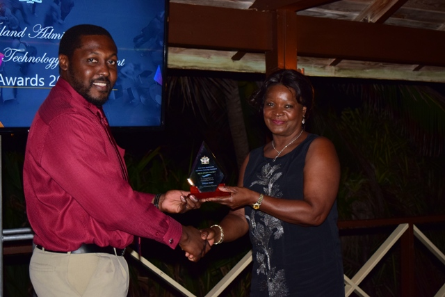 Craig David, Assistant Director at the Information Technology Department in the Nevis Island Administration, receiving the Ticketeer Award on behalf of Vanessa Tyson from Mrs. Verni Amory, wife of the Premier of Nevis Hon. Vance Amory, at the 2nd Annual Information Technology Department Delta Awards Dinner at the Nisbet Plantation Beach Hotel on February 18, 2017