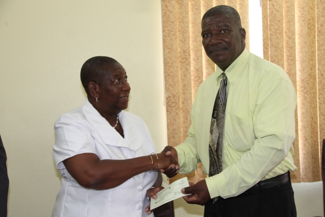 Dr. Robertine Chaderton, Chairman of the St. Kitts and Nevis Sugar Industry Diversification Foundation Board of Counsellors, presents a cheque to Edson Elliott, Principal of the Charlestown Secondary School and the Nevis Sixth Form College, at a ceremony at the Ministry of Finance conference room in Charlestown on February 17, 2017, to assist with hosting the Leeward Islands Debating Competition
