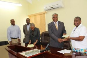 Dr. Robertine Chaderton, Chairman St. Kitts and Nevis Sugar Diversification Foundation hands over a cheque to Hon. Vance Amory, Premier of Nevis and Minister of Finance in the Nevis Island Administration at the Ministry of Finance conference room in Charlestown on February 14, 2017. It is the second draw-down from funds for the construction of the 400 meter athletic Mondo track at Long Point. Looking on are (l-r) Counsellors Leon Lescott and Delara Taylor and Secretary to the Board Marguerite Foreman