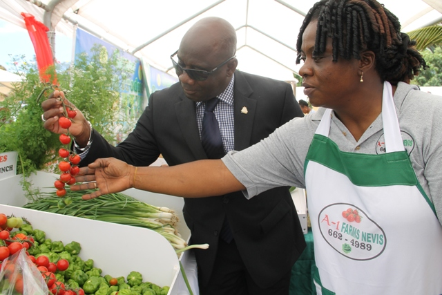Minister of Agriculture on Nevis Hon. Alexis Jeffers takes a closer look at local produce with Mrs. Fayola Tross from A1 Farms Nevis at the 23rd Annual Agriculture Open Day hosted by the Ministry and Depart of Agriculture in the Nevis Island Administration at the Villa Grounds, Charlestown on March 30, 2017