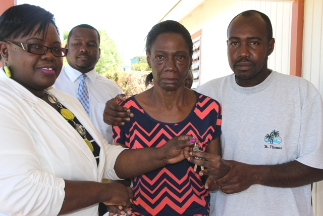 Junior Minister in the Ministry of Social development Hazel-Brandy Williams hands keys to a new home to Ms. Lynette Koram at Jessups Village on March 10, 2017, flanked by her son care taker Lesroy Koram. Looking on is Permanent Secretary in the Ministry of Social Development Keith Glasgow